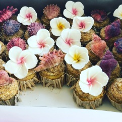 Moana Themed Cupcakes with Edible Plumerias, Shells, and Sand. Finished with Hula Skirt Decor.